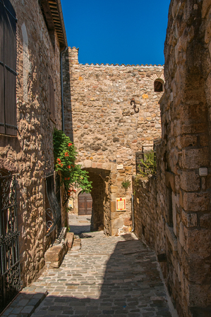 View of stone houses in a narrow alley under blue sky, at the gorgeous medieval hamlet of Les Arcs-sur-Argens, near Draguignan. Located in the Provence region, Var department, southeastern France Reklamní fotografie