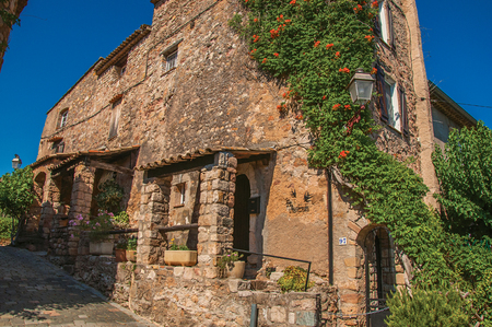 Les Arcs-sur-Argens, France - July 10, 2016. View of stone house facade with bindweed in the gorgeous medieval hamlet of Les Arcs-sur-Argens. Provence region, Var department, southeastern France Stock Photo