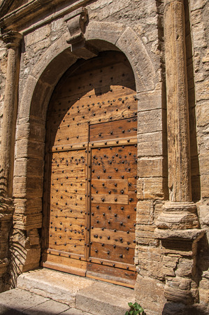 Wooden door and stone arch in ancient Chateaudouble church, a quiet and tourist village with medieval origin on a sunny summer day. Located in the Var department, Provence region, southeastern France