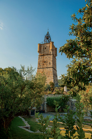 View of the clock tower made of stone on top of the hill with vegetation in the lively and gracious town of Draguignan. Located in the Var department, Provence region, southeastern France Banque d'images - 94878041