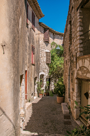 View of alley with stone houses and slope in Saint-Paul-de-Vence, a lovely well preserved medieval hamlet near Nice. Located in Alpes-Maritimes department, Provence region, southeastern France