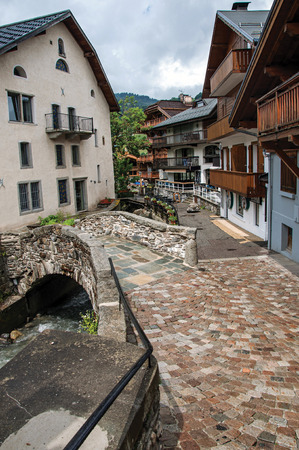 Typical buildings in the cobblestone street with little bridge and alpine view. Cloudy day at Megeve near the Mont Blanc in the French Alps. Editorial