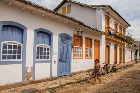 Paraty, Brazil - January 26, 2015. Cobblestone alley with colorful old houses and woman in Paraty, an amazing and historic town totally preserved in Rio de Janeiro State, southwestern Brazil Editorial