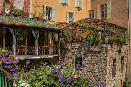 Moustiers-Sainte-Marie, France - July 08, 2016. Restaurant with flowers and stone walls in the lovely village of Moustiers-Sainte-Marie. Provence region, southeastern France