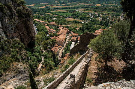View of stone staircase, roofs and belfry under sunny blue sky in the charming village of Moustiers-Sainte-Marie. In the Alpes-de-Haute-Provence department, Provence region, southeastern France