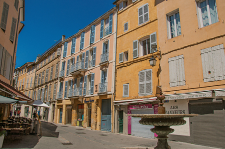 Aix-en-Provence, France - July 09, 2016. Alley with colorful buildings, shop and fountain in Aix-en-Provence, a pleasant and lively town in the French countryside. Provence region, southeastern France