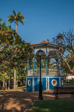 Sao Manuel, southeast Brazil - September 08, 2017. Old colorful gazebo in the middle of full garden of trees, in a sunny day at San Manuel. A cute little town in the countryside of Sao Paulo State.