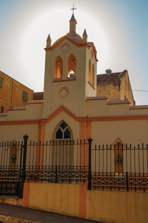 Facade of small church and belfry, behind iron fence, with sunshine behind at sunset in San Manuel. A cute little town in the countryside of São Paulo State. Southeast Brazil. Retouched photo.