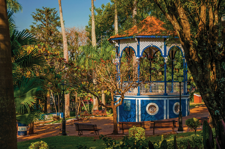 Sao Manuel, southeast Brazil - September 08, 2017. Old colorful gazebo in the middle of full garden of trees, in a sunny day at San Manuel. A cute little town in the countryside of São Paulo State.