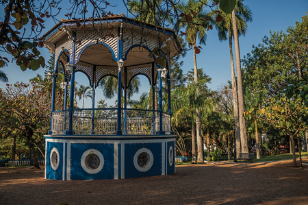 Old colorful gazebo of square in the middle of verdant garden full of trees, at sunset in San Manuel. A cute little town in the countryside of Sao Paulo State. Southeast Brazil.