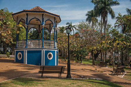 Old colorful gazebo and lighting pole in the middle of verdant garden full of trees, in the sunny day at San Manuel. A cute little town in the countryside of São Paulo State. Southeast Brazil.