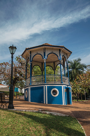 Old colorful gazebo and lighting pole in the middle of garden with green lawn, in a sunny day at San Manuel. A cute little town in the countryside of Sao Paulo State. Southeast Brazil.