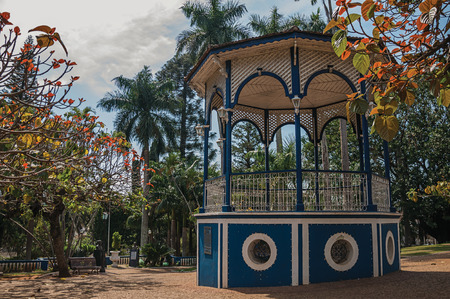 Old and colorful gazebo in a small square amid verdant garden full of trees, in the sunny day at San Manuel. A cute little town in the countryside of Sao Paulo State. Southeast Brazil. Stock Photo