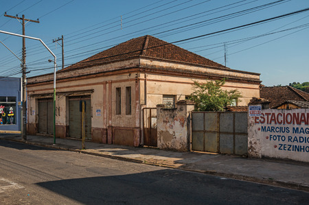 Sao Manuel, southeast Brazil - October 14, 2017. Outworn old house and wall with painted placard in empty street on the sunset at San Manuel. A cute little town in the countryside of São Paulo State