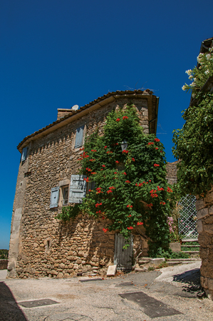 Menerbes, France - July 07, 2016. View of typical stone house with sunny blue sky and flowers, in an alley of the historical village of Menerbes. In the Provence-Alpes-C?'te d'Azur region.