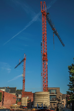 Construction area with cranes at sunset and bright blue sky in Tielt. Charming and quiet village in the countryside, near Ghent and surrounded by agricultural fields. Western Belgium.