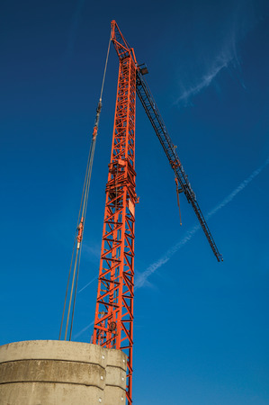 Close-up of crane in a blue sky at sunset. Charming and quiet village in the countryside, near Ghent and surrounded by agricultural fields. Western Belgium. Reklamní fotografie