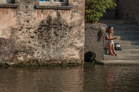 Ghent, Belgium - July 03, 2017. Woman taking ice cream sitting on staircase in front of canal in Ghent. In addition to intense cultural life, the city is full of Gothic buildings. Northern Belgium.