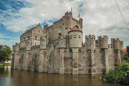 Lake and stone wall in front of Gravensteen Castle on cloudy day in Ghent
