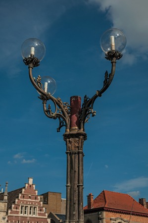 Close-up of cast iron lamp post and sunny blue sky in the City Center of Ghent. In addition to intense cultural life, the city is full of Gothic and Flemish style buildings. Northern Belgium.