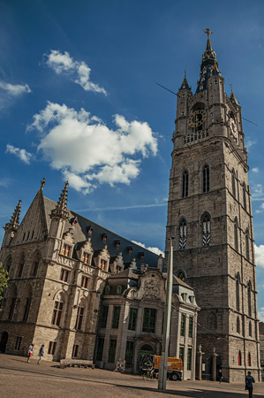 Ghent, Belgium - July 03, 2017. People, Gothic cathedral with clock tower in Ghent. In addition to intense cultural life, the city is full of canals and buildings in Flemish style. Northern Belgium.