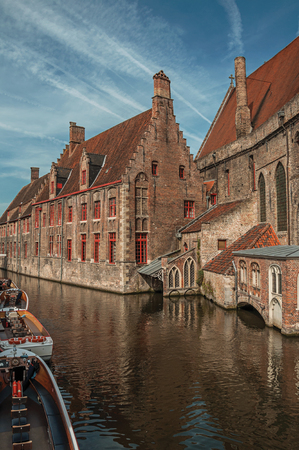 Old buildings on the canal bank, boats and sunny blue sky in Bruges. With many canals and old buildings, this graceful town is a World Heritage Site of Unesco. Northwestern Belgium.