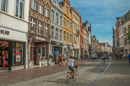 Bruges, Belgium - July 05, 2017. Street with people, brick houses and shops in Bruges. With many canals and old buildings, this graceful town is a World Heritage Site of Unesco. Northwestern Belgium.