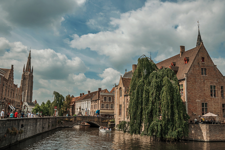 Bruges, Belgium - July 05, 2017. People and old buildings on the canals edge at Bruges. With many canals and old buildings, this graceful town is a World Heritage Site of Unesco. Northwestern Belgium Editorial