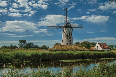 Old windmill next to canal with bushes and grove in the background in late afternoon light and blue sky, near Damme. A quiet and charming countryside near Bruges. Northwestern Belgium. Stock Photo