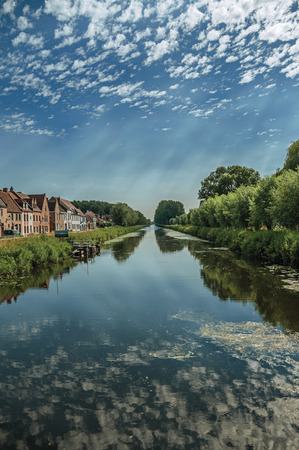 Houses, bushes and grove along canal with sky reflected on water, in the late afternoon and blue sky, near Damme. A quiet and charming countryside near Bruges. Northwestern Belgium.