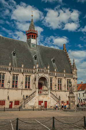 Damme, northwestern Belgium - July 05, 2017. Gothic-style building of the town hall and people in the central square of Damme. A quiet and charming countryside near Bruges.