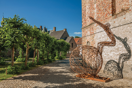 Rusted iron artwork in front of brick wall and pathway with trees under sunny blue sky at Damme Stock Photo