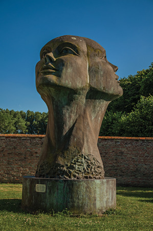 Damme, northwestern Belgium - July 05, 2017. Big statue of two cast heads in garden of medieval church ruins under sunny blue sky at Damme. A quiet and charming countryside near Bruges.