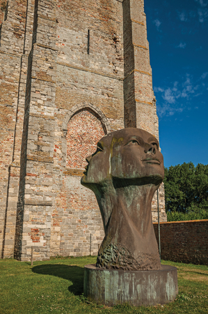 Big statue of two cast heads in garden of medieval church ruins under sunny blue sky at Damme Stock Photo