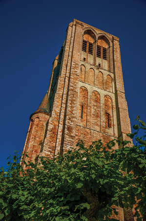 Brick bell tower in garden of medieval church ruins, in the late afternoon light at Damme