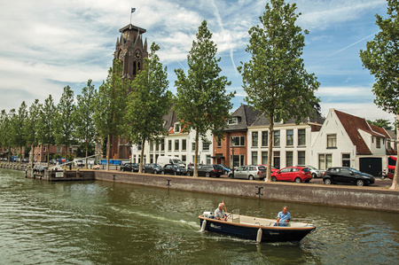 Boat passing by wooded wide canal with brick houses and sunny blue sky in Weesp. Quiet and pleasant village full of canals and green near Amsterdam.