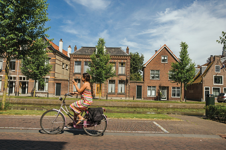 Woman pedaling bicycle in street on the edge of channel on sunny day in Weesp. Quiet and pleasant village full of canals and green near Amsterdam.