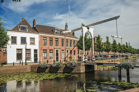 Canal with street on the banks, brick houses and bascule bridge on a sunny day in Weesp. Quiet and pleasant village full of canals and green near Amsterdam
