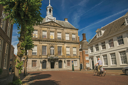 Elder man biking on street in front of the City Hall building on sunny day in Weesp. Quiet and pleasant village full of canals and green near Amsterdam.