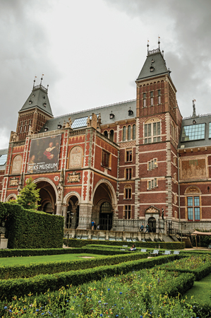 Garden and Rijksmuseum (National Museum) facade with people and cloudy sky in Amsterdam. City with huge cultural activity, graceful canals and bridges.