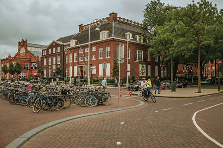 Parked bicycles and cyclist doing curve in street with cloudy sky at Amsterdam. Famous for its huge cultural activity, graceful canals and bridges.