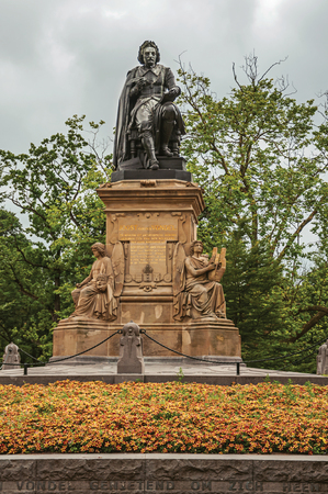 Flowers and monument with the statue of Joost Van Den Vondel in Amsterdam park. Famous for its huge cultural activity, graceful canals and bridges.