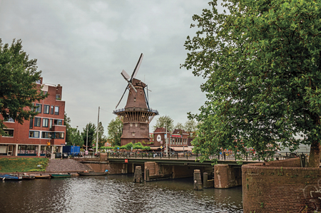 Bridge over canal, trees and old windmill on the bank with cloudy sky in Amsterdam. Famous for its huge cultural activity, graceful canals and bridges. Northern Netherlands.