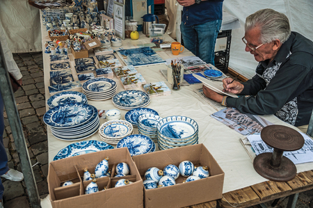 Skilled artisan hand-painting crockery in the region typical style at Gouda. Very popular day trip destination, is famous for its tasty Gouda cheese. Editorial