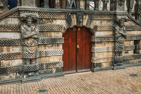 Statues around wooded door in front of the gothic City Hall building of Gouda. Very popular day trip destination, is famous for its tasty Gouda cheese