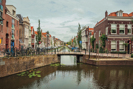 Tree-lined long canal with small bridge, brick houses on its bank and cloudy day at Gouda. Very popular day trip destination, is famous for its tasty Gouda cheese. Southern Netherlands. Editorial