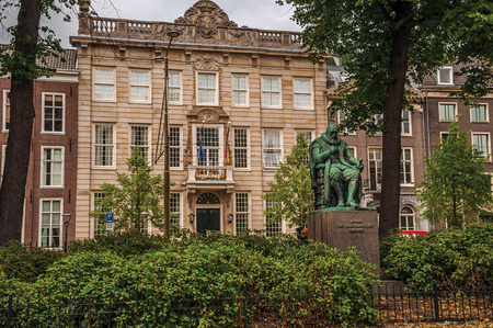Bronze statue, garden with leafy trees in front of brick buildings and cloudy sky in The Hague. Important political center, is a mix of historic city with modernity. Western Netherlands.