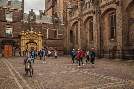 People in the Binnenhof (Gothic public buildings) inner courtyard at The Hague. Important political center, is a mix of historic city with modernity. Banco de Imagens - 99590744