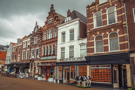 Market Square and old brick building facade with cheese shop on cloudy day in Delft. Calm and graceful village full of canals and Gothic architecture. Editorial