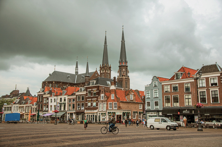 People on Market Square, brick buildings with shops and steeple on cloudy day in Delft. Calm and graceful village full of canals and Gothic architecture.